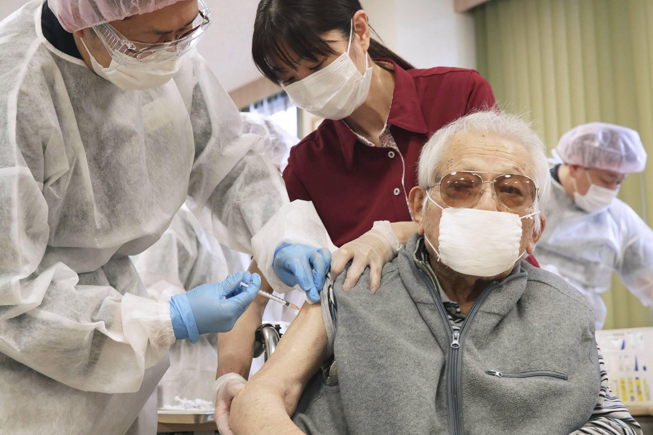 Muž dostane vakcínu COVID-19 v ošetřovatelském zařízení v tokijském Setagaya Ward 12. dubna